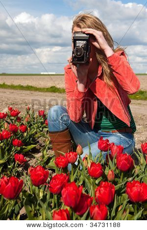 Portrait of a beautiful blond Dutch girl taking pictures in tulips field