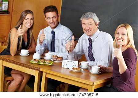 Four happy business people holding their thumbs up in a caf�©