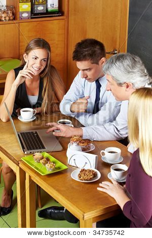 Happy business people having a meeting with laptop in a caf�©
