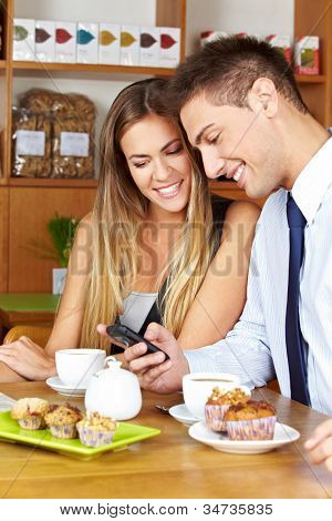 Smiling business couple with smartphone sitting in a caf�?�©