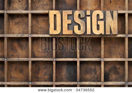 design word in vintage letterpress wood type against divider pattern of a grunge typesetter case