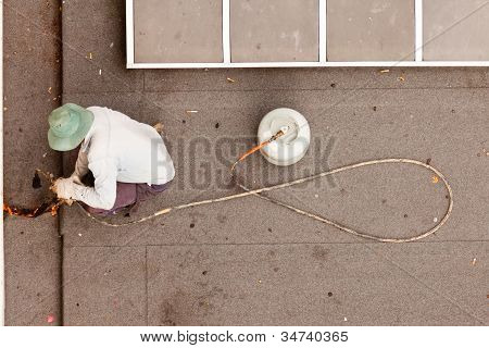 Roofer using propane torch to repair flat roof