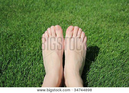 pés femininos em um gramado verde