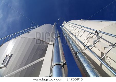 Two white silos against blue sky