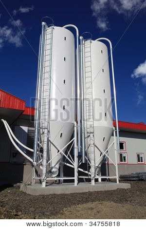 Two modern silos in front of barn