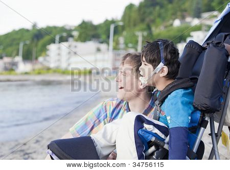 Father Enjoying  Beach With Disabled Son