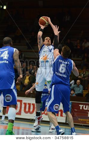 KAPOSVAR, HUNGARY - FEBRUARY 22: Jozsef Lekli (in white) in action at a Hungarian Cup basketball game with Kaposvar (white) vs. Fehervar (blue) on February 22, 2012 in Kaposvar, Hungary.