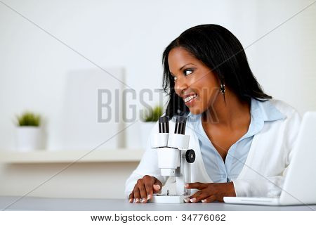 Charming Young Woman Using A Microscope