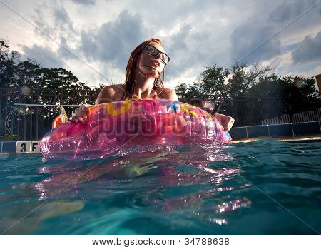 Young Woman Playing And Swimming In A Pool