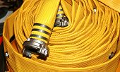 stock photo of hookup  - Folded fire hose of yellow color with the cap nut - JPG