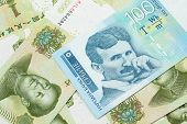 A Close Up Of A Blue And White, One Hundred Serbian Dinar Bank Note On A Background Of Chinese One Y poster