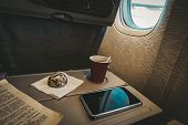 Entertainment During Flight. Monotonous Pastime During The Flight. Coffee, Gingerbread, A Book And A poster