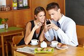 Business people in caf�?�© with smartphone having a meeting