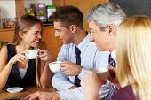 Four smiling business people taking a break with coffee in a caf�?�©