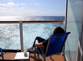 stock photo of fantail  - Balcony of Stateroom with passenger relaxing on Deck Chair on Transatlantic cruise - JPG