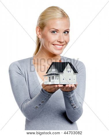 Half-length portrait of girl in grey pullover with small model house, isolated on white