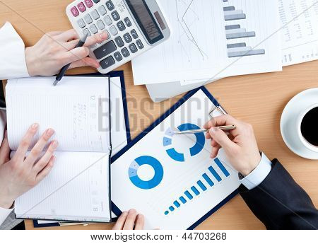 Business people working with documents sitting at the table. Close up of hands