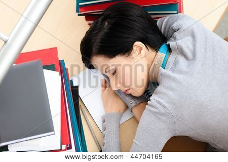 Female student sleeping at the desk with piles of books. Tired of studying. Top view