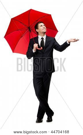 Palming up man with opened umbrella checks the rain, isolated on white