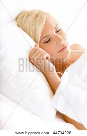 Close up shot of sleepy woman in bed lying on the white cushion