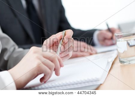 Business people making notes in notebooks sitting at the table. Close up view of hands