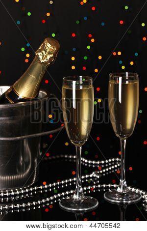 Champagne luminosa con copas sobre fondo de luces de Navidad