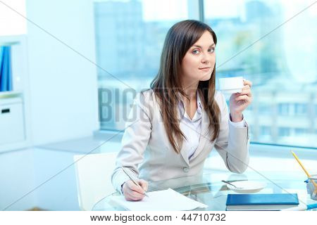 Portrait of young female drinking tea while writing proficiency test