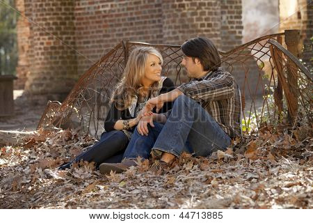 beautiful couple talking while sitting in fall leaves