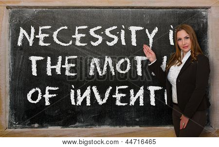 Teacher Showing Necessity Is The Mother Of Invention On Blackboard