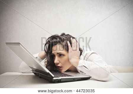 desperate businesswoman with hands in her hair fixed laptop