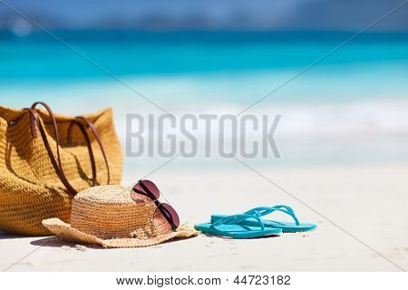 Straw hat, bag, sun glasses and flip flops on a tropical beach