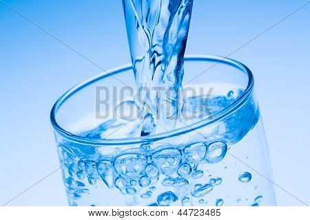 pour water into a glass, symbolic photo for drinking water, excess and waste