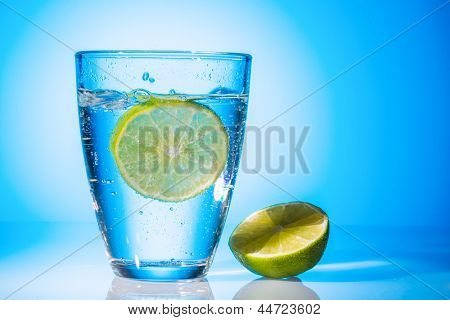 a glass of fresh drinking water and a lime. mineral water as a thirst quencher.
