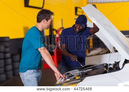 african auto mechanic and customer discussing vehicle fault