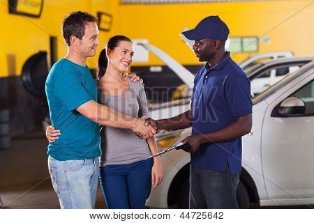 african auto technician handshaking with young couple in garage