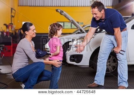 cute little girl hiding auto technician's hat in garage