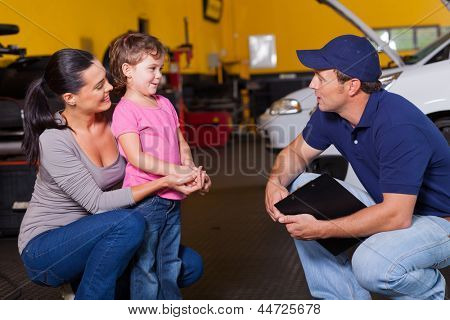friendly auto technician talking to customer's little daughter in garage