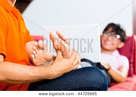 Indonesian couple sitting home on sofa, she using the laptop for emails and internet, he is massaging her feet