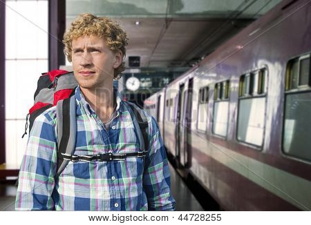 Young man with a backpack ready to embark on a journey by train