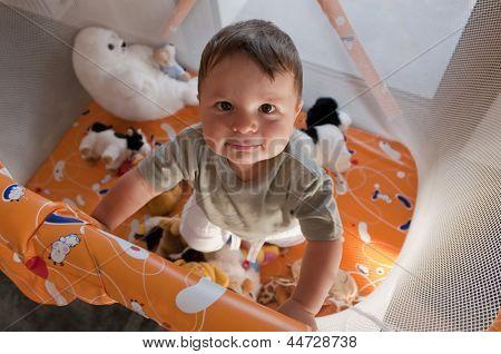 Portrait of a cute baby in playpen