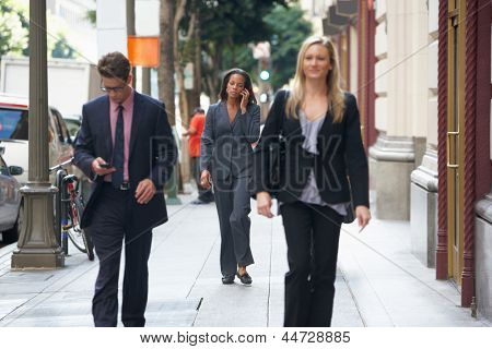 Group Of Businesspeople Walking Along Street