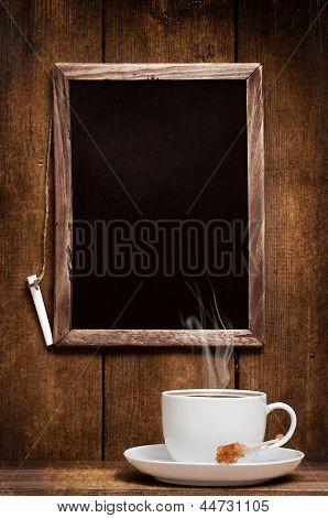 Cup of steaming coffee against menu board