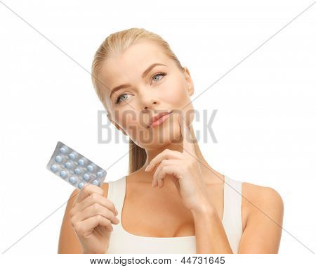 picture of thoughtful young woman with pills