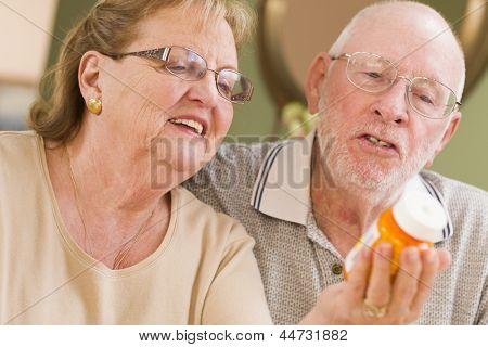 Curious Senior Couple Reading Prescription Medicine Bottle Together.
