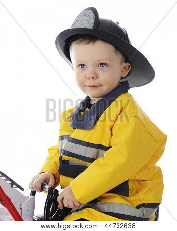 Close-up image of an adorable toddler boy dressed as a fireman.  On a white background.
