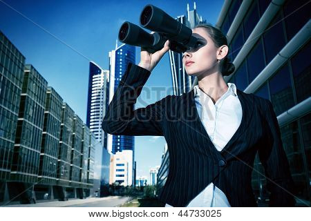 Business woman standing in the big city and purposefully looking through the binoculars.