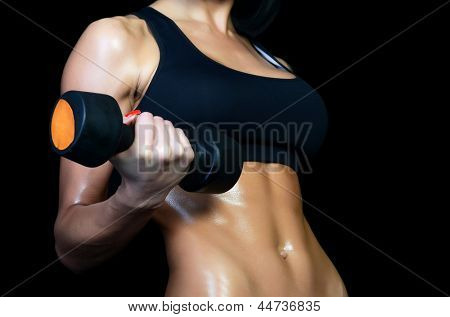 Beautiful brawny body of woman with dumbbells