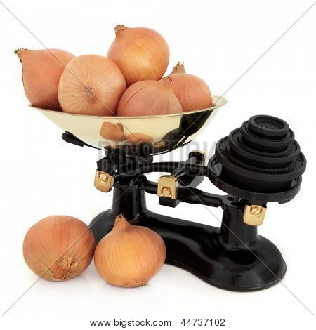 Onion vegetables and retro cast iron scales with imperial weights over white background.