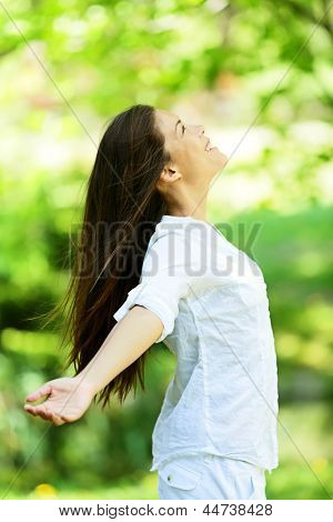 Young woman embracing the arrival of spring standing in a leafy green park with her arms outspread and her head raised to the heavens as she rejoices in nature. Enjoyment and freedom concept.