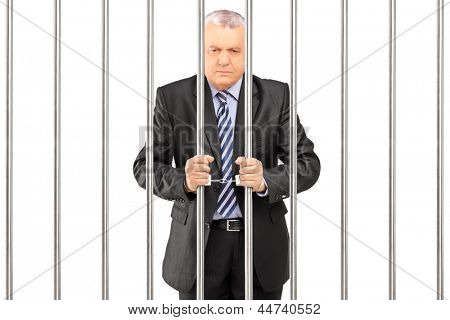 A handcuffed manager in suit posing in jail and holding bars, isolated on white background